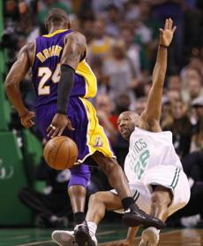 The Lakers' Kobe Bryant drives Celtics guard Sam Cassell into the floor in the second quarter of Game 1.