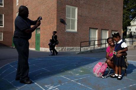 Olayemi Phillips takes a photo of her daughter Nia and husband Charles on Nia's first day of school at Chittick Elementary School in Mattapan.
