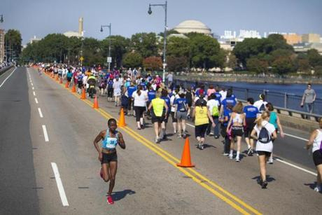 10/10/11 - Boston, MA - Cherobon-Bawcom, cq, of Rome, GA, who opened up a huge lead from the rest of the pack returned over Massachusetts Avenue bridge during the latter half of the race. On the right are runners in the earlier stages of the race. The Tufts Health Plan 10K for Women took place on the Boston Common on Monday, October 10, 2011 at noon. Topic: Tufts 10 K. Dina Rudick/Globe Staff.