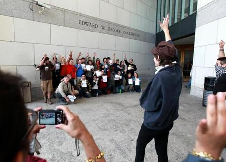 Boston, MA - 10/11/11 - Occupy Boston members who were arrested late last night pose for a photo outside the rear entrance to the Edward W. Brooke Courthouse after they were released today after paying a $50.00 court assessed fee. While posing for the photo one member shouted