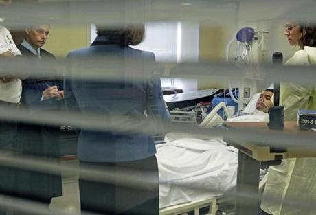 10-12-11 Burlington, MA: POOL PHOTO BY JIM DAVIS/BOSTON GLOBE......... NOTE: PHOTO WAS SHOT THROUGH A GLASS WINDOW WITH OPEN BLINDS......Antonio Matos was arraigned in his hospital bed this afternoon at Lahey Clinic in Burlington for the shooting of Woburn police officer Robert DeNapoli (not pictured) following a jewelry store robbery. Judge James Barretto is at left, assistant district attorney Marian Ryan is next to the judge, and defense attorney Julie Buszuwski is at right. (Globe Staff Photo/Jim Davis) section: metro slug:13matos