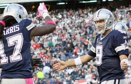 FOXBORO, MA - OCTOBER 16: Tony Romo #9 of the Dallas Cowboys celebrates the touchdown with teammate Dwayne Harris #17 in the first half against the New England Patriots on October 16, 2011 at Gillette Stadium in Foxboro, Massachusetts. (Photo by Elsa/Getty Images)