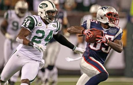 11-13-11: East Rutherford, NJ: Patriots wide reciver Chad Ochocinco leves the Jets Darrelle Revis in the backround as he heads for a first down on the 18 yard line with a long first quarter pass completion. The New England Patriots visited the New York Jets in a regular season NFL game at MetLife Stadium. (Globe Staff Photo/Jim Davis) section:sports topic:unknown