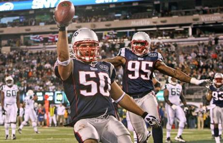 11-13-11: East Rutherford, NJ: Patriots linebacker Rob Ninkovich (50) returned a fourth quarter interception for a touchdown that helped seal the Patritos victory. Teammate Mark Anderson (95) in the backround. The New England Patriots visited the New York Jets in a regular season NFL game at MetLife Stadium. (Globe Staff Photo/Jim Davis) section:sports topic:unknown
