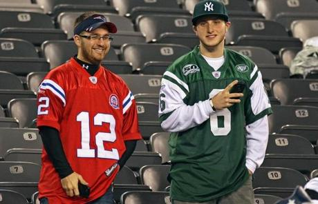 11-13-11: East Rutherford, NJ: Two fans (one dressed in a Tom Brady jersey (left) and one in a Mark Sanchez jersey (right) hang out together in the stands before the game. The New England Patriots visited the New York Jets in a regular season NFL game at MetLife Stadium. (Globe Staff Photo/Jim Davis) section:sports topic:unknown