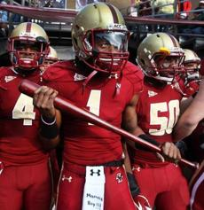Boston College wide receiver Colin Larmond Jr. carries a         baseball bat onto the field during pregame introductions at         Alumni Stadium, Nov. 12, 2011—''Well, it all started in the         Friday night meeting with the players. The captains speak to the         team and then the other players, if they have something to say,         can talk. [Offensive lineman] Bryan Davis was telling us that         before he left to go to school, he gave hismoma baseball bat and         said, 'If anyone tries to break into the house, use the baseball         bat and swing.' He related it to how on Saturday we're playing a         game—the last home game and senior day against the [North         Carolina State] Wolfpack. He said, 'You know the wolves are         going to come into our house and attack in packs and what were         we going to do to keep them out?' He had that baseball bat and         he said, 'Seniors, you better go out swinging,' and he gave me         the bat. So I just ran out on the field with the bat and we did         come out swinging, so I guess that's our newlittle bat now. I         want to say it's a Louisville Slugger . . . Oh, and that Mama's         Boy on the towel, that's because I grewup with mymom[in         Morristown, N.J.], who was a single mother, so I'mnot afraid to         say I am a mama's boy.''