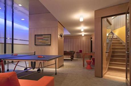 In a lower-level Brookline game room designed by Andra Birkerts, a Mylar ceiling reflects color and brightens the space.