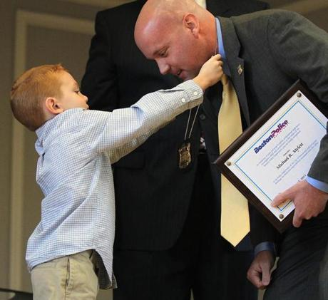 Michael Mylett, 6,  presented his father, Boston police officer Michael Mylett, with his detective's badge during a ceremony at the Hyde Park Municipal Building.