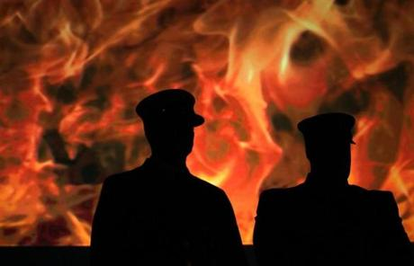 West Bridgewater firefighters were silhoueted against a video screen of fire during the annual Massachusetts Firefighter of the Year Awards at the Hanover Theatre in Worcester.