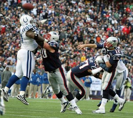 12-04-11: Foxboro, MA: Patriots OL Logan Mankins keeps a leaping Colts DL Antonio Johnson (left) away from quarterback Tom Brady long enough to let Brady throw his first touchdown pass of the game in the second quarter, a 11 yard scoring strike to TE Rob Gronkowski (not pictured). The New England Patriots hosted the Indianapolis Colts in an NFL regular season game at Gillette Stadium. (Globe Staff Photo/Jim Davis) section:metro topic:patriots