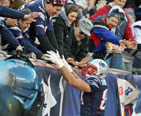 12-04-11: Foxboro, MA: Patrots tight end Rob Gronkowski high fives with end zone fans the crowd as he celebrates his second touchdown of the game , that (with the PAT) made the score 24-3 New England in the third quarter. The New England Patriots hosted the Indianapolis Colts in an NFL regular season game at Gillette Stadium. (Globe Staff Photo/Jim Davis) section:metro topic:patriots