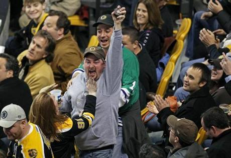 12-19-11: Boston, MA: A Bruins fan is excited after he caught a puck that sailed into the stands . The Boston Bruins hosted the Montreal Canadiens in a regular season NHL game at the TD Garden. (Globe Staff Photo/Jim Davis) section:sports topic:Bruins LOID # 5.0.666764699