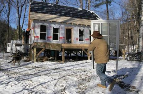 Stockbridge, VT - 12-18-11- Don Fielder (cq) carries a window to his new home to be installed by family and friends. Don Fielder (cq) with the help from family and friends, rebuilds after his home was destroyed during the floods of Tropical Storm Irene. (Globe staff photo / Bill Greene) section:met, reporter:filipov, topic:25irene
