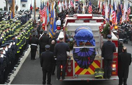 Peabody, Mass. -12/30/11 - Funeral services were held for Peabody firefighter James M. Rice at St. John The Baptist Church, as hundreds of firefighters from all over came to pay respect. His casket is carried on engine5 at the ne of the funeral service which leaves the church.Globe staff photo by John Tlumacki (metro)