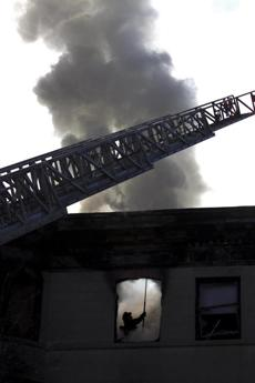 A firefighter cleared debris and burning pieces of the interior of a unit after the roof had collapsed in Brookline. Jan. 16, 2012.
