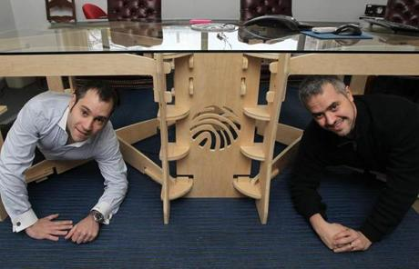 Cambridge, MA 1/12/12 CustomMade Ventures Corp (cq) cofounder and CFO Seth Rosen (cq), left, and cofounder and CEO Mike Salguero (cq) pose with the conference table they designed with Raleigh, NC maker Jeffrey Sgroi (cq). (The company's logo is routed into the hard plywood.) Michael Margolis (cq) (not shown), with Google Ventures, works on user-experience testing in the