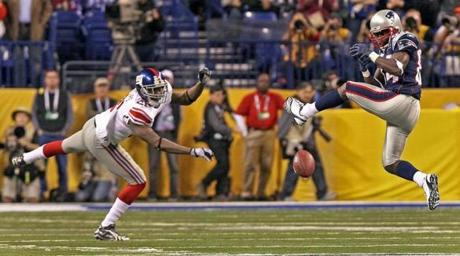02-05-12: Indianapolis, IN: The Patriots Deion Branch drops a pass from Tom Brady on the final drive of the game, the GiantsKenny Phillips is at left. The New England Patriots meet the New York Giants in Super Bowl XLVI at Lucas Oil Stadium. Section: Sports topic:Super Bowl (Globe Staff Photo/Jim Davis)