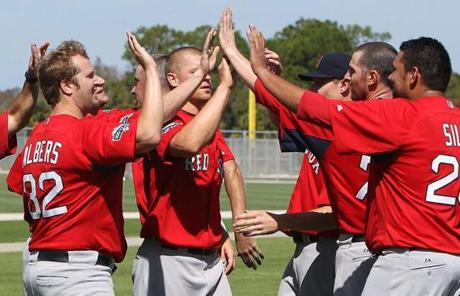 A group of pitchers celebrated with high-fives after wind sprints early in camp.