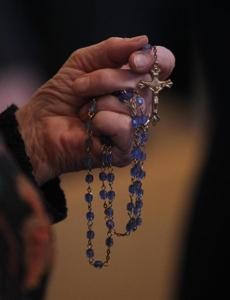 Geraldine Shea, who attends Holy Trinity in Quincy, prayed with her rosary during a Mass at St. Joseph the Worker. Her 8-year-old granddaughter, from Pembroke, will soon receive her First Eucharist in the Hanson church.