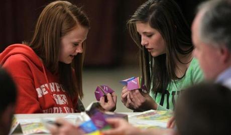 "Cassie Hickie (left) and Erin Wengryn, both 13, worked with ""identity catchers"" in one of the break-out groups led by teacher Joe Rice during a lesson."