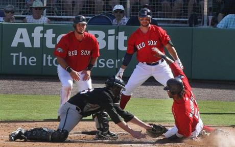 Red Sox outfielder Darnell McDonald (right) slides safely into home past Northeastern catcher Tucker Roeder in the inaugural game at JetBlue Park in Fort Myers, Fla., March 3, 2012.