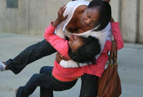A woman tried to control a screaming relative outside the courthouse as verdicts were read in the first Mattapan massacre trial. March 22, 2012.