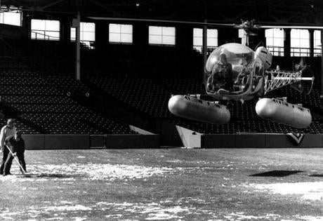 Grounds crew members got assistance from a helicopter in tending to the field on April 11, 1974.
