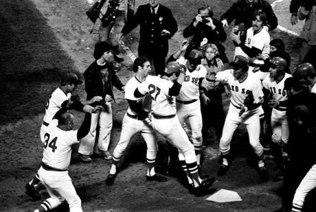 Carlton Fisk jumps on home plate with the game-winning run after his walk-off home run in Game 6 of the 1975 World Series.