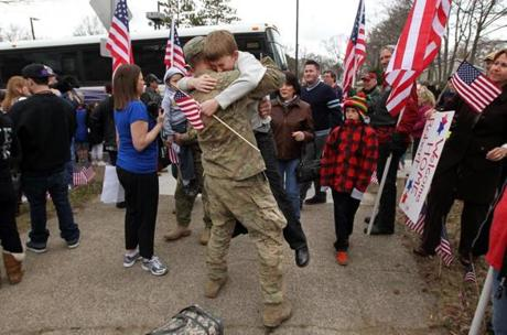 Robert McCarthy of Braintree greeted his 10-year-old son, Liam, at the Braintree Armory.