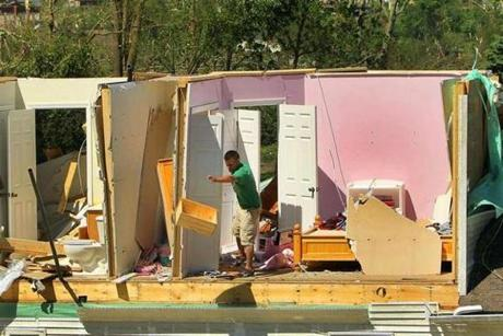 A homeowner sifts through belongings from the shell of a second floor home on Heritage Lane. (June 2, 2011)