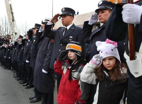 Alex White, 8, and his friend, Paige Biscaia, 6, both from Salem, were allowed to stand in front of firefighters as they saluted the fallen firefighter in Peabody Square. (Dec. 30, 2011)