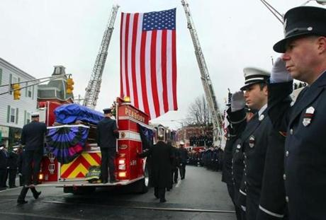Firefighters salute as Rice's casket is carried in the back of the fire truck he was assigned to. (December 30, 2011)