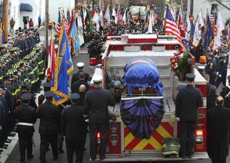 Engine 5,  carrying the casket of firefighter Jim Rice,  leaves the church at the end of services. (Dec. 30, 2011)