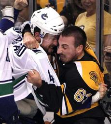 Bruins' Brad Marchand fights with Vancouver's Keith Ballard late in third period action during game 4 of the Stanley Cup Finals. (June 8, 2011)