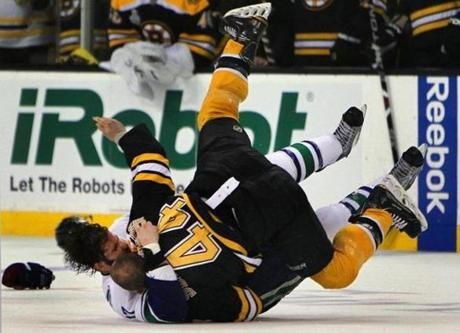 Bruin's Dennis Seidenberg and Vancouver's Ryan Kesler fight in third period action in game 3 of the Stanley Cup Finals. (June 6, 2011)