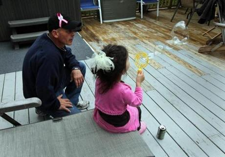 Gloucester, MA - 5-10-12 - Anthony Harrison (cq) watches his daughter Lizzie (cq) blow bubbles at the Harrison home. His other daughter Caleigh Harrison (cq) is missing. (Globe staff photo / Bill Greene) section:g, reporter:english, Topic: harrison