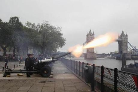 Guns fire in a 41 gun salute at the Tower of London in front of Tower Bridge.