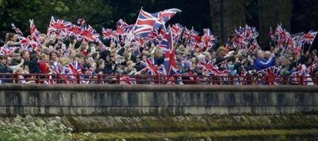 People lining the river bank waved British Union flags as members of the British royal, embarked on the royal barge.