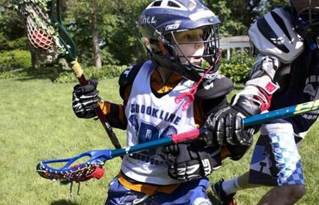 Beau Keough, 9, played lacrosse with his older brothers in their Brookline back yard. The Keough brothers love the sport and its culture.