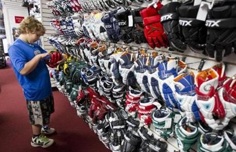 Liam Peck, 9, of Sherborn, checked out a new glove at Comlax, a one-stop lacrosse store in Needham, on Friday.
