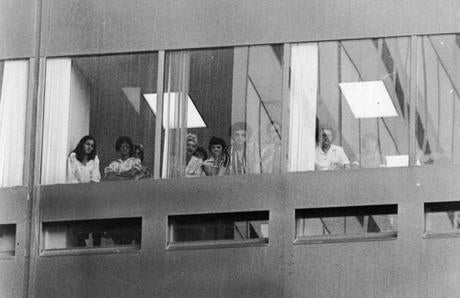 June 28, 1978:  Curious employees in the Blue Cross office building at 100 Summer Street look down at the scene of the murders of five men in the Blackfriars Pub basement. The bodies were found by Jerry Robinson, a night cleaner shortly after 7 a.m. The Boston Globe reached him by phone only minutes after he had made the grim discovery and called police.