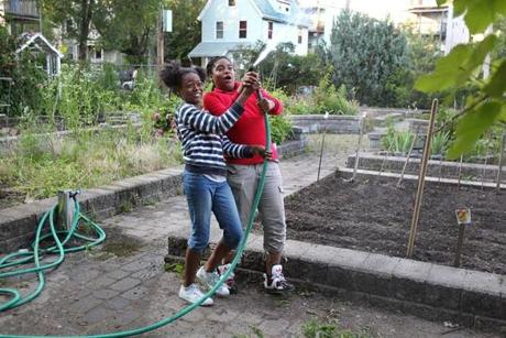 Friends Kaori Tate, 10, left, and Ghiyahna Ennis, 11, share a plot in the garden on Coleman Street. They help other gardeners and water for them when their plots look dry. On this June night, the garden was full of people, many of them planting vegetables.