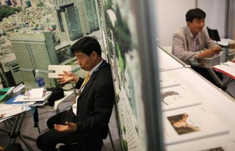 Representatives from different Korean biotechnology companies meet in separate booths.