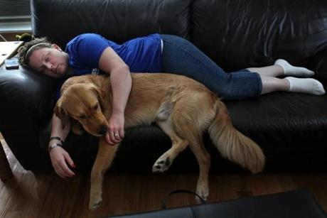 Marine Corps veteran Natasha Young-Alicea of Haverhill returned from working at the Vet Center with a migraine and tried to get some relief resting on her couch with her service dog Josh. June 25, 2012.