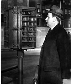 Joseph J. O'Brien, the cashier in charge of toll collection at the Sumner Tunnel, examines the toll recorder on December 23, 1940. When a toll was handed over, the least being 15 cents for a pleasure car and the most a dollar for a truck 10 tons or over, with a variety of amounts in between, lights would flash on the indicator pictured here which would tell the driver the tollman has just recorded the amount paid on his electrically operated toll register. When the tunnel opened the toll was 25 cents for cars but was lowered to 15 cents when the Chelsea North Bridge was closed in January 1935..