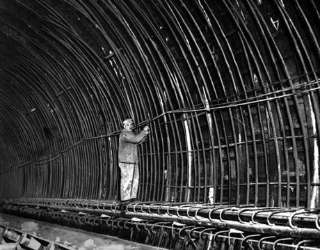 In the East Boston tunnel , a worker on April 10, 1932 ties in the reinforcing rods of the curved ceiling that will be buried in the concrete.  Reports of the concreting of the tunnel at the time said that the level of safety was such that if the outside coating of cement between the steel and the mud were to wear away and if the steel itself were to corrode to nothing, this inside 18-inch wall of concrete would still stand and make a safe tunnel.