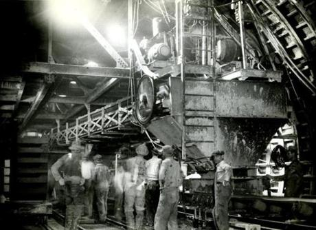 In the East Boston tunnel, a conveyor carries the clay and other material from the shield on January 14, 1932. The shield was a round device of steel about 15 feet long and a little more than 31 feet in diameter. In the front part of the shield the actual work of excavation was done. As fast as the clay was removed, the shield advanced  This big conveyor consisted of a wide belt running over rollers. Along the conveyor ran a steady stream of clay which the muckers burrowed out. The conveyor belt dropped the clay into a huge elevator consisting of a chain of wide buckets. The elevator then carried the clay to the surface where it dropped into waiting trucks and was taken to fill the space around the then East Boston Airport.