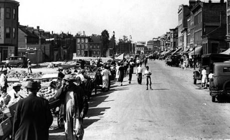 In East Boston, an open-air market is strung out along the line of the broad approach then under construction to the East Boston portal of the new traffic tunnel on September 30, 1933.  On the Boston end, transformation was also taking place as building  wreckers tore down buildings and widened streets around Haymarket Square.