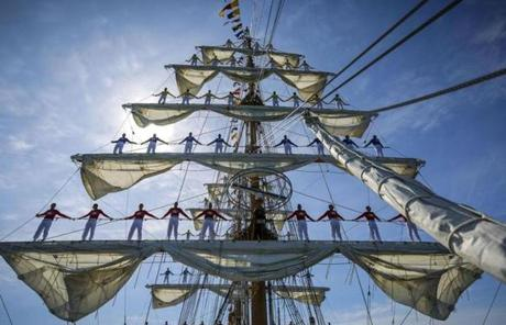 Midshipmen stood along the rigging of the ARC Gloria.