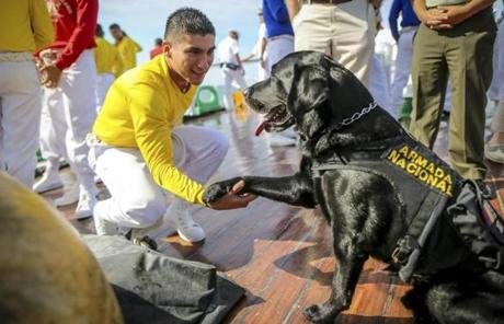 Midshipman Juan Sebastian Sanchez shook the paw of Colombia's ARC Gloria's dog, Argos.